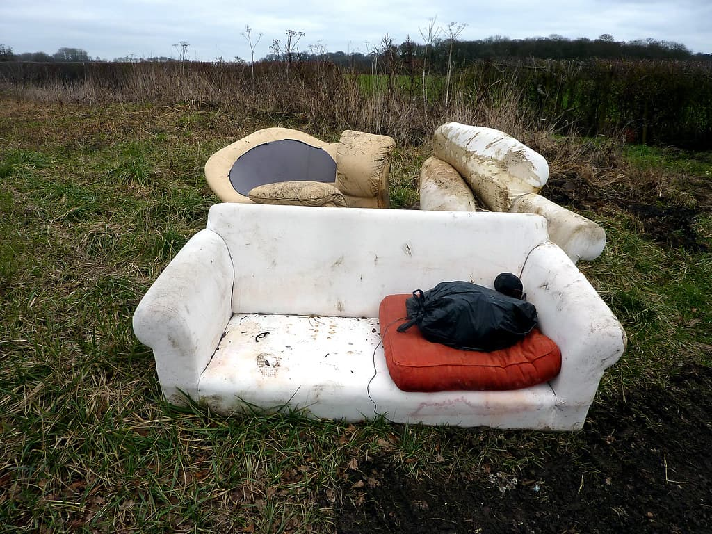 flytipped rubbish on field comprising sofa and cushions