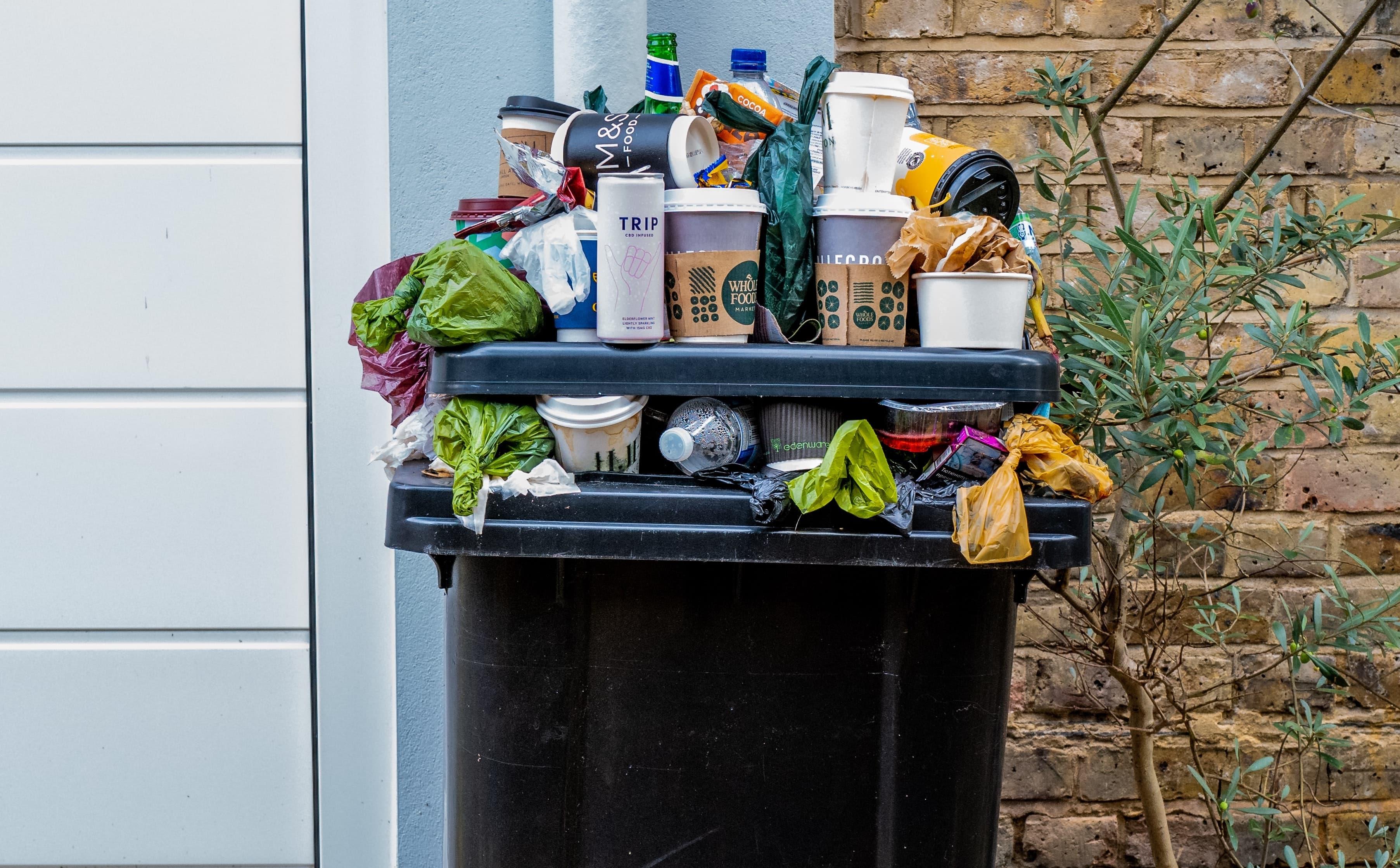 overflowing wheelie bin too much waste