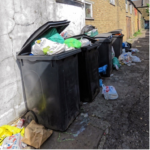 overflowing rubbish black wheelie bins on residential street