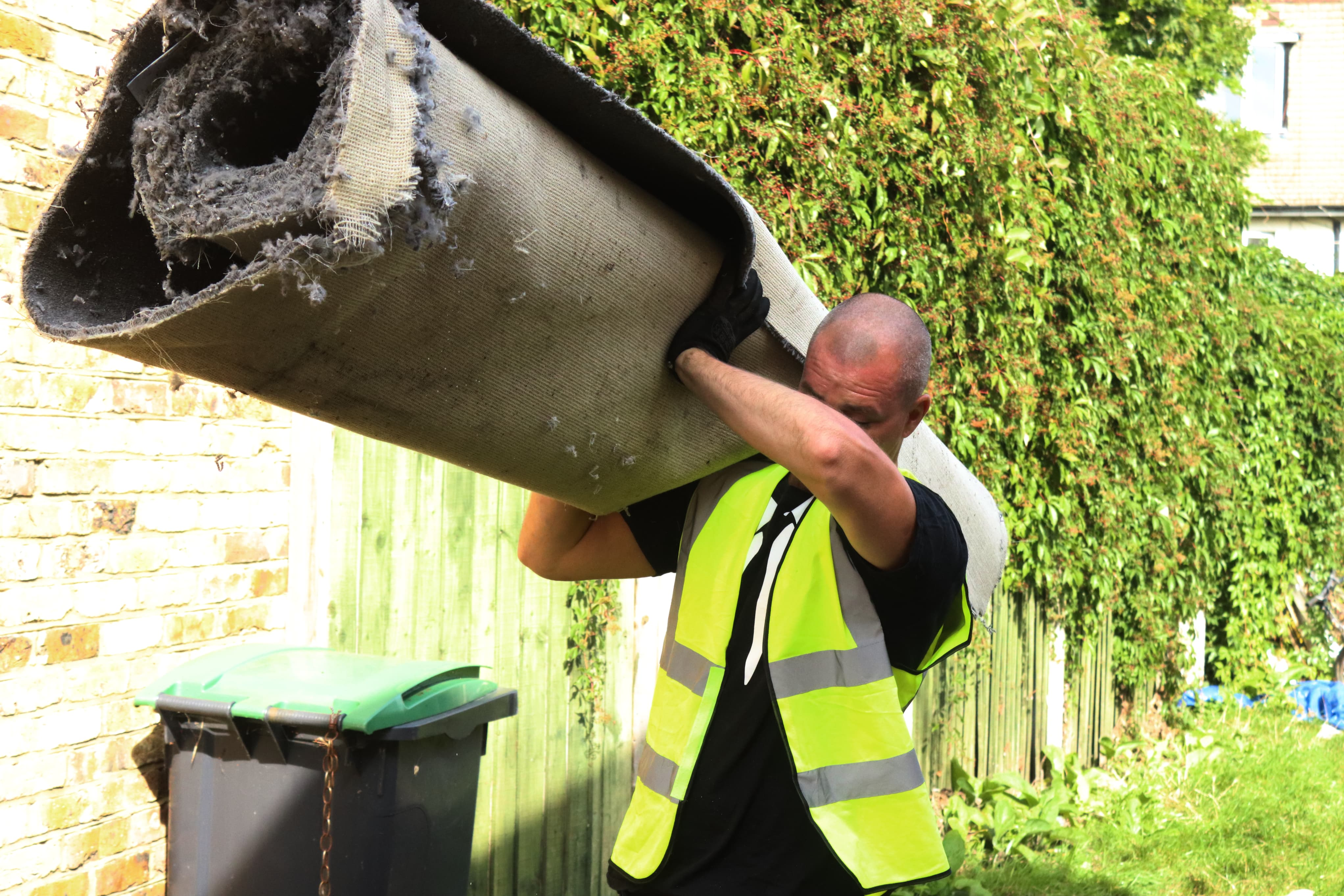 man and van clearance compamny carrying rolled up carpet for carpet disposal